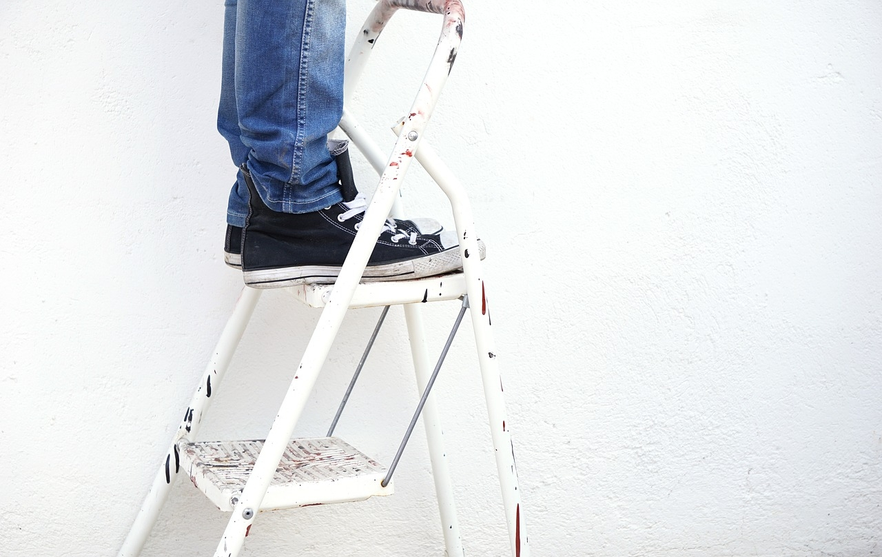 Top step of a ladder, jeans and converse shoes
